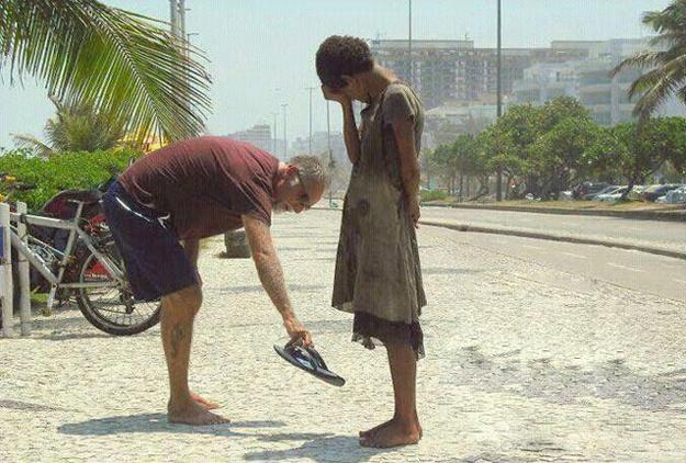 A man giving his shoes to a homeless girl in Rio de Janeiro