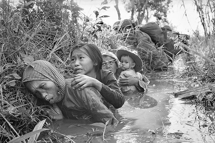 Photograph Horst Faas/AP Women and children crouch in a muddy canal as they take cover from intense Viet Cong fire on 1 January 1966. Paratroopers of the 173rd Airborne Brigade (background) escorted the civilians through a series of firefights during the US assault on a Viet Cong stronghold at Bao Trai, about twenty miles west of Saigon