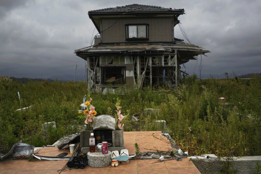 a-small-monument-to-victims-is-seen-in-front-of-an-abandoned-house-at-the-tsunami-destroyed-coastal-area