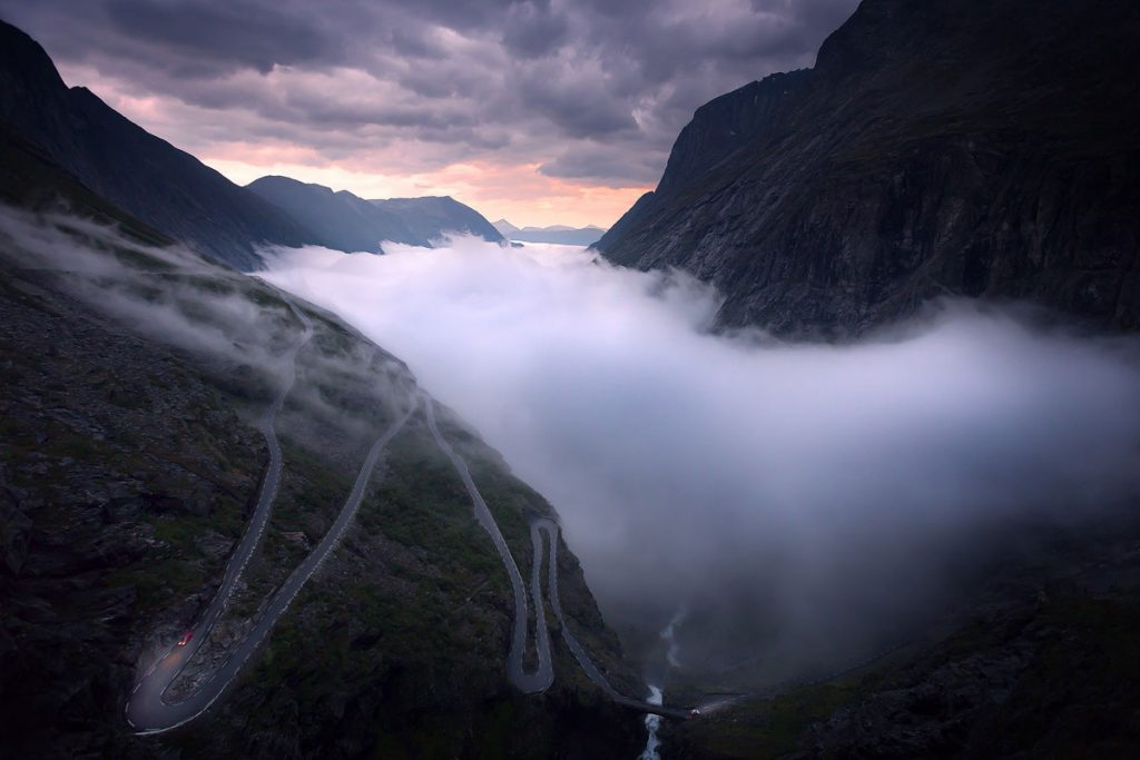 © Sean Ensch / National Geographic Traveler Photo Contest         The mountain road, Trollstigen, in western Norway. I was lucky enough to live here for two months during summer and one evening I saw the valley filling with fog, so I drove up the road to watch the late summer midnight sun set as the fog swayed through the valley below.